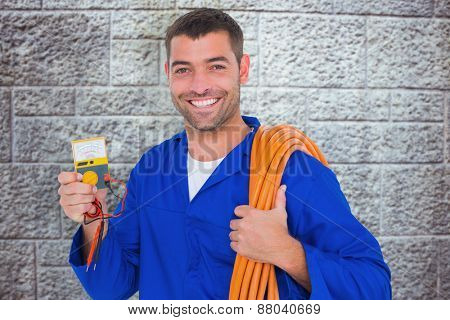 Smiling electrician with rolled wire and multimeter against grey brick wall
