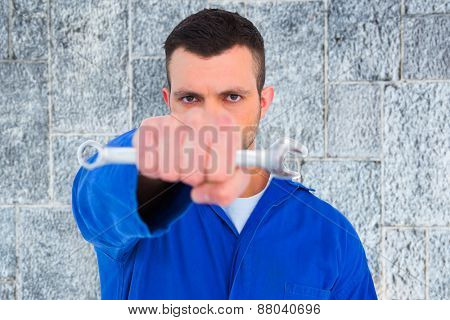 Confident male mechanic holding spanner against grey