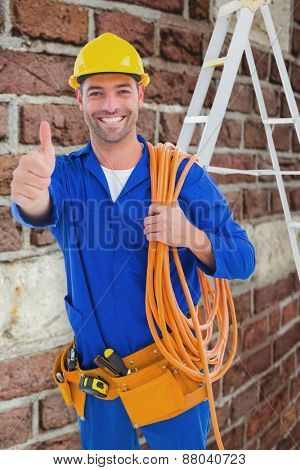 Male technician with wire roll gesturing thumbs up against red brick wall