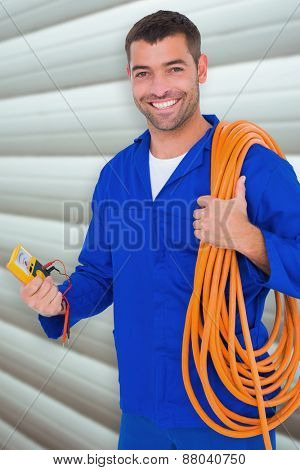 Smiling electrician with wire roll and multimeter against grey shutters