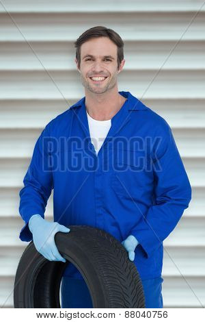 Confident mechanic holding tire against grey shutters