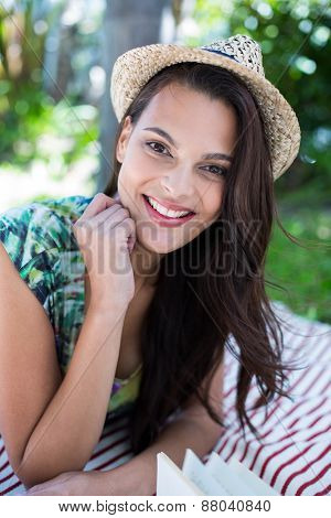 Smiling beautiful brunette lying on the blanket with palm tree behind her