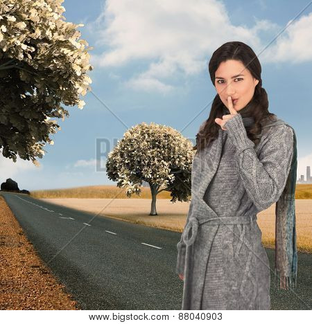 Young model with winter clothes keeping secret against road leading out to the horizon