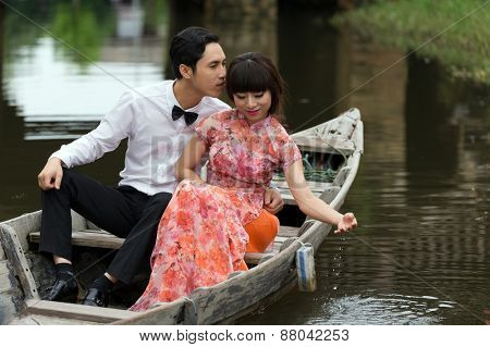 HOI AN, VIETNAM, DECEMBER 14, 2014: A young couple is celebrating his wedding on a wooden boat in the city of Hoi Han, Vietnam.