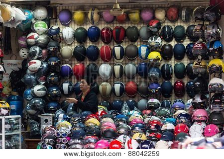 HANOI, VIETNAM, DECEMBER 15, 2014:A woman is specialized in the selling of motorbike helmets in her street shop in Hanoi, Vietnam