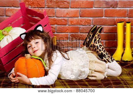 Baby Lying On The Floor, Hugging A Pumpkin