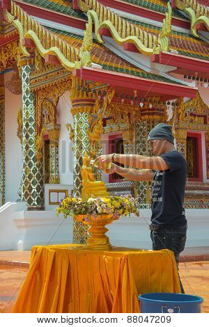 Young man with him descendant are pouring water onto Buddha image.
