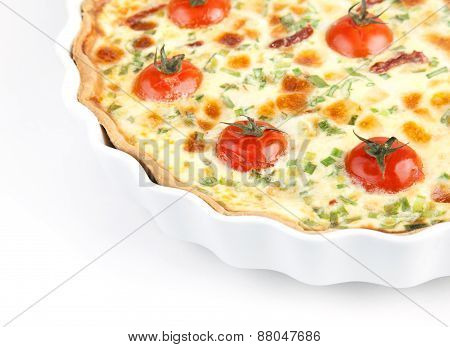 Quiche with cherry tomatoes and herbs on a white plate