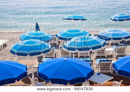Blue umbrellas and chairs on pebble beach in Nice, France.