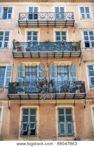 Facade of apartment building with ornate balconies in Nice, France.