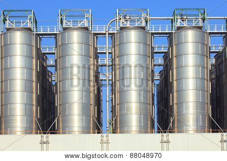 Metal Steel Tank Storage In Heavy Industry Estate Plant Against Clear Blue Sky Use For Industrial An
