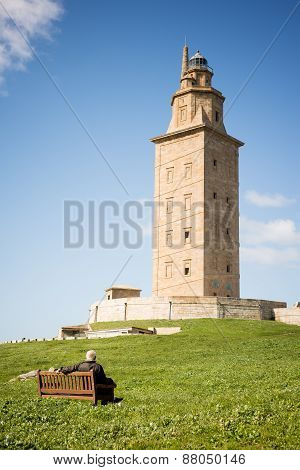 Man Contemplating Hercules Tower Lighthouse In La Coruna, Spain.