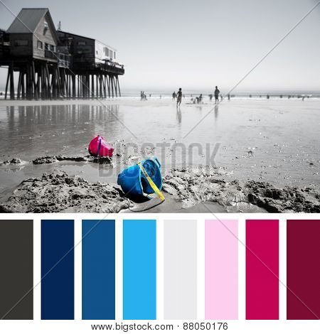 Discarded children's buckets on Old Orchard Beach, Maine, USA. Faded effect photo with selective colour highlighting the buckets. In a colour palette with complimentary colour swatches.