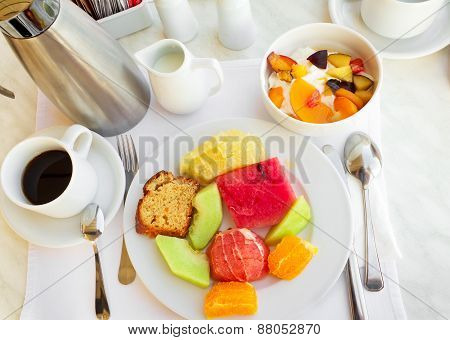 Fruit dessert - diverse fruits and berries, black coffee.