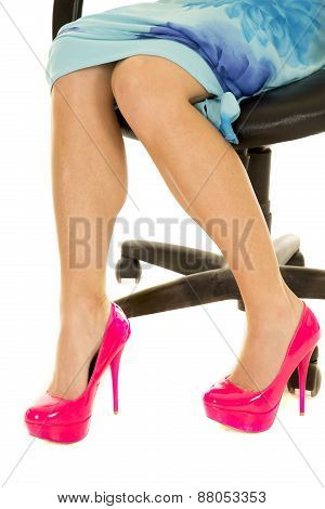 Woman Legs In Pink Heels And Blue Dress Sitting Feet Pointed To Side