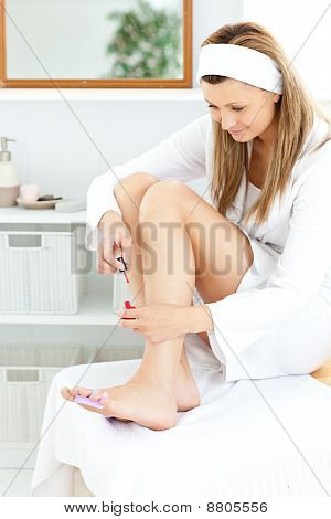 Delighted Young Woman Varnishing Her Toenails In The Bathroom