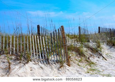 Weathered beach fence in white sand dunes