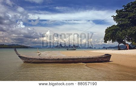 Long boat on the beach among tropical islands