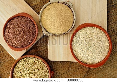 high-angle shot of some earthenware bowls with amaranth, quinoa, brown flax and buckwheat seeds on a rustic wooden table