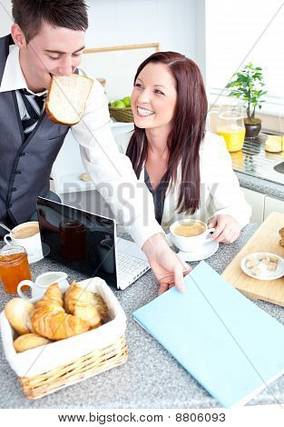 Cheerful Couple Ob Businesspeople Having Breakfast In The Kitchen