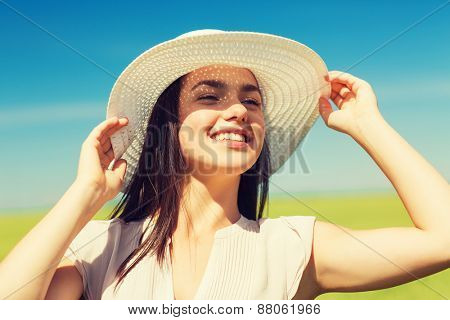 happiness, nature, summer, vacation and people concept - smiling young woman wearing straw hat in nature