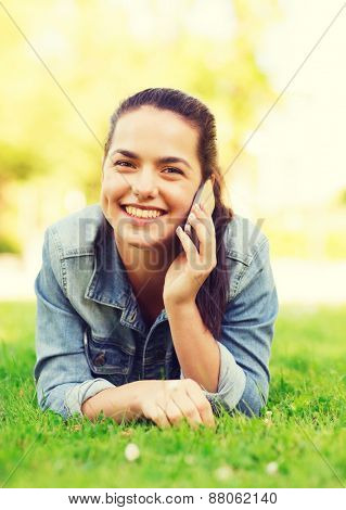lifestyle, summer vacation, technology, leisure and people concept - smiling young girl with smartphone talking and lying on grass in park