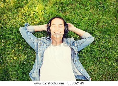 lifestyle, summer vacation, technology, music and people concept - smiling young girl in headphones lying with closed eyes on grass