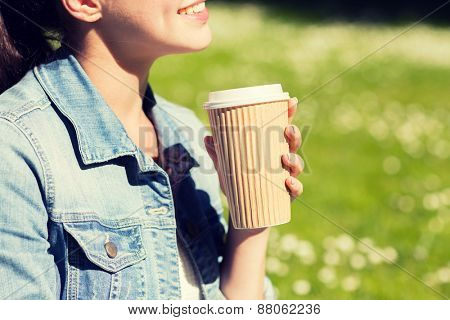 lifestyle, summer vacation, leisure, drinks and people concept - close up of smiling young girl with coffee cup in park
