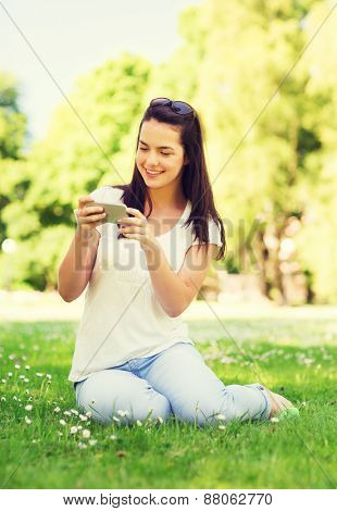 lifestyle, summer, vacation, technology and people concept - smiling young girl with smartphone sitting on grass in park