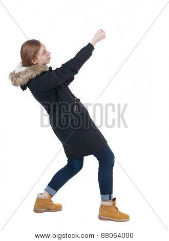 Side view. girl in winter jacket pulls his hands on top of the rope   Standing young girl in parka. Rear view people collection.  backside view of person.  Isolated over white background.