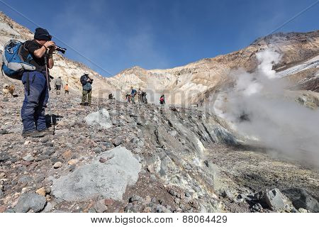 Photographers Takes A Picture Volcanic Landscape In Crater Mutnovsky Volcano. Kamchatka