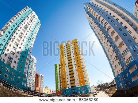 Tall Apartment Buildings Under Construction Against A Blue Sky Background