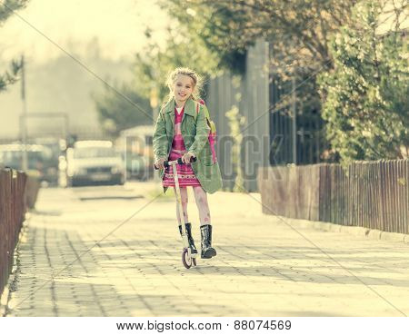 girl goes to school on a scooter