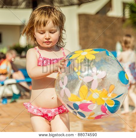 little cute girl playing near the pool with a ball closeup