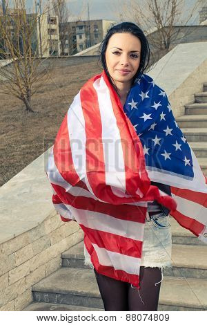 Younf latino women warped in US flag outdoors patritic concept