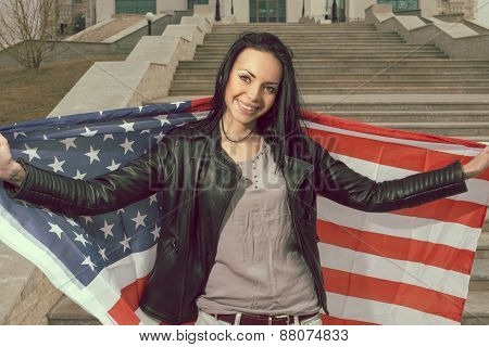 Young happy women with us flag outdoors smiling widely