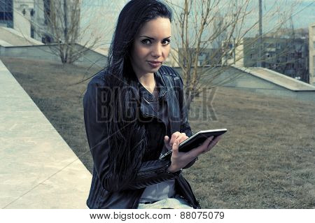 Brunette with tablet pc in autumn park looking at camera