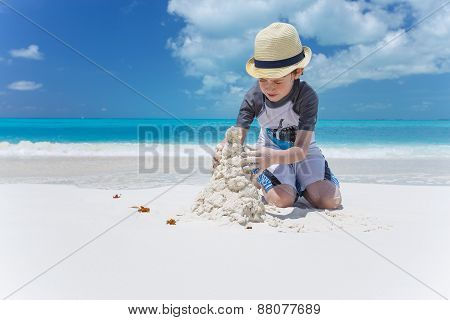 Little Child Making Sand Castles At The Beach