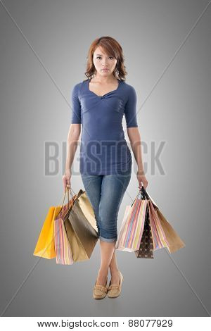 Confident shopping woman of Asian holding bags, isolated.