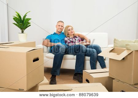 Couple In New Home Relaxing On Couch