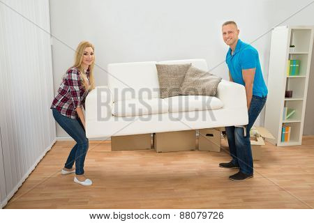 Young Couple Carrying Couch