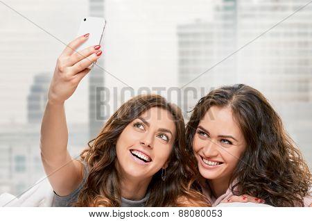 Smiling girls making selfie at home