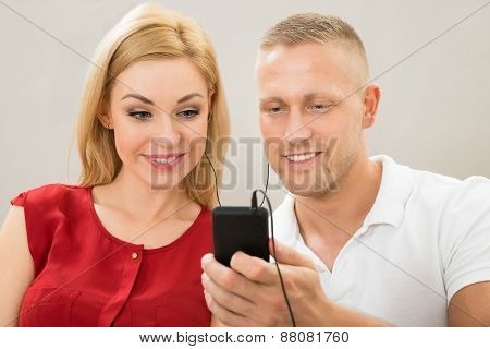 Couple Listening To Music With Mobile Phone
