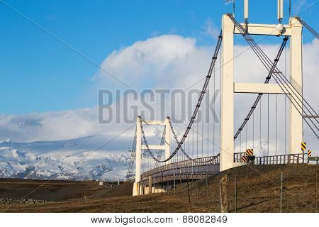 A modern suspension bridge connects the shore line disrupted by the glacier lagoon in Iceland.