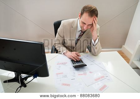 Businessman Calculating Unpaid Bills