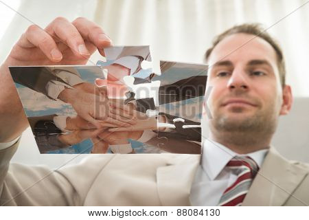 Businessman Inserting Last Puzzle Piece