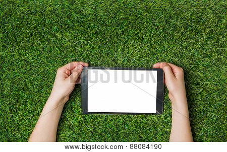 Child hands holding tablet pc. over green grass