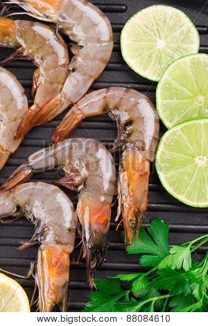 Raw shrimps on black pan.