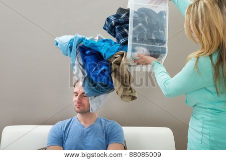 Woman Throwing Laundry On Husband