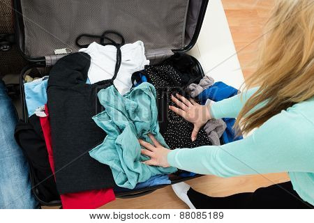 Woman Packing Clothes In Suitcase